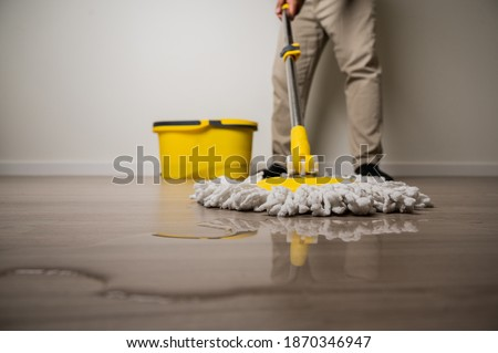 Cleaning workers mopping the wet area. There was spill water on the wooden floor in the living room. Zdjęcia stock ©
