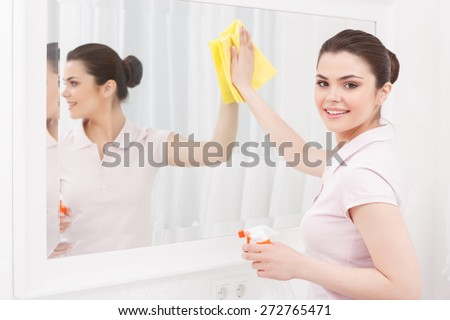 Cleanness in every move. Pretty brunette cleans mirror with help of yellow cloth and special mean of cleaning on white background