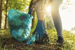 Cleanup volunteer collecting trash in the forest and holding a garbage bag, environmental protection concept
