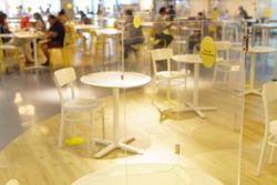 Clear acrylic or plastic divider, barrier or partition on empty table in food court or restaurant as part of safety protection for customers. New normal, social distancing during Covid-19 pandemic