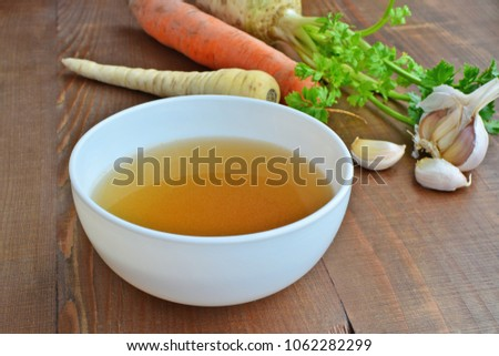 Clear beef broth, bone broth, bouillon in white bowl and vegetables on wooden table
