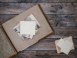 Clear blank photo frames to placed your pictures or text on old family album on wooden board background in retro style. Family traditions, memories and nostalgia concept. Antique album with old photos