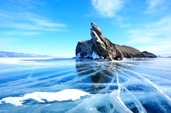 Clear blue frozen lake baikal with mountains during winter in Siberia, Russia