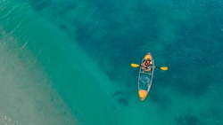 clear blue sea with floating transparent kayak, person with life jacket on boat