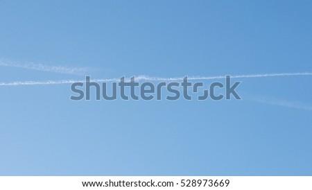 clear blue sky with aeroplane trails #528973669
