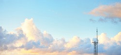 Clear blue sky with glowing pink and golden cumulus clouds after storm at sunset. Dramatic cloudscape. Concept art, meteorology, heaven, hope, peace, graphic resources, picturesque panoramic scenery