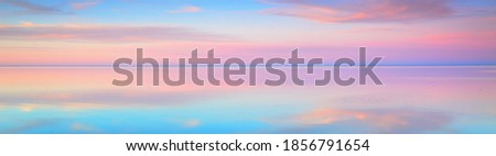 Clear blue sunset sky with glowing pink clouds above the sea. Symmetry reflections on the water, natural mirror. Breathtaking panoramic scenery. Idyllic landscape. Climate change, beauty in nature