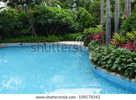 Clear blue water in large swimming pool with trees.