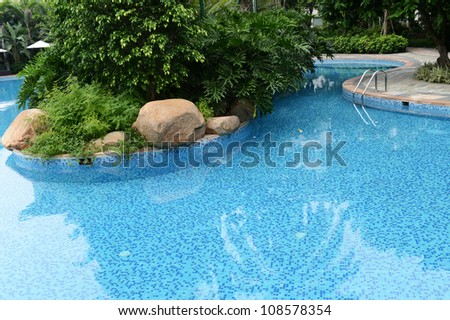 Clear blue water in large swimming pool with trees. - stock photo