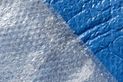 Clear bubblewrap texture on blue plastic postal bag ready to send.