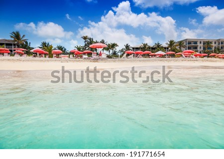 Clear calm waters lap the white sands of an umbrella studded Grace Bay Beach, Turks and Caicos