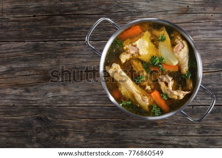 clear Chicken broth with pieces of rooster meat on bone and vegetables in a metal casserole on dark wooden table, view from above