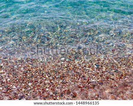 clear clear sea water and pebble beach