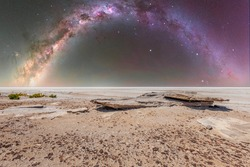 Clear cloudless night landscape of Kati Thanda - Lake Eyre in the deserts of central Australia with rocks in the foreground and background sky with bright stars of the galaxy