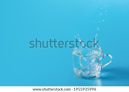 Clear cold water in a glass cup on a blue background. Beautiful splash from falling ice Foto stock ©