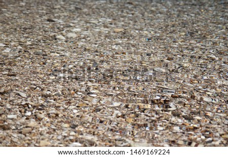 Clear crystal clear water on the beach with light pebbles
