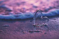 clear glass heart on  sand beach with sunrise sun light, Canary island, Spain
