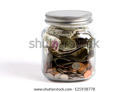Clear glass jar filled with USA dollars and coins sit on a white background financial concept.