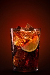 Clear glass of fresh appetizing drink with ice cubes and sliced citrus on burgundy background