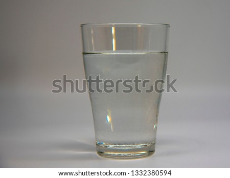 clear glass with clear water on grey background.