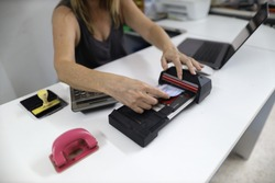 Clear image of female hand inserting  imprinting paper with credit card underneath into old pre-digital credit card imprinter machine white office table background