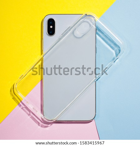 Photo of  Clear iPhone case mock up. Smart phone on a background of pink, yellow and blue paper, silicone transparent case back view mockup