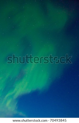 Clear night sky with lots of stars and dancing northern lights (Aurora borealis).