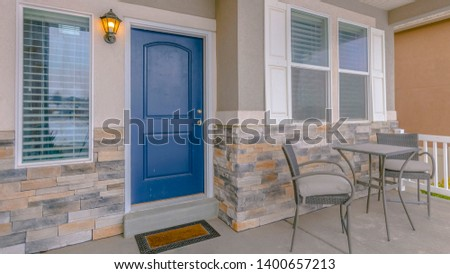 Clear Panorama Exterior of a home with blue wooden front door and reflective glass windows