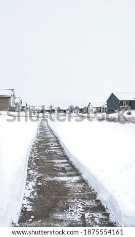 Clear pathway swept from thickness of white snow blizzard. The perspective of long concrete walkway. Beautiful quiet meadow outdoor landscape with clear sky in winter season 商業照片 ©