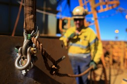 Clear pictures of Bow D Shackle defocused trained rigger wearing safety helmet, work uniform using two way radio and holding a tagline while communicating with crane operator load is being lifted