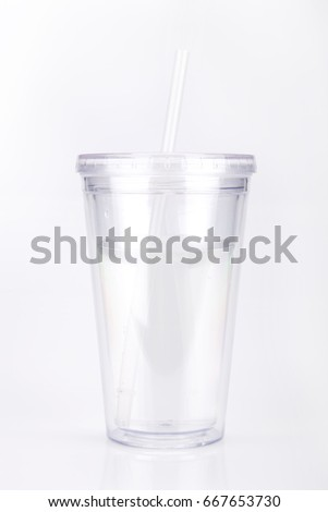 Clear plastic tumbler glass with lid and straw on a white surface. Travel cup isolated on white background.
