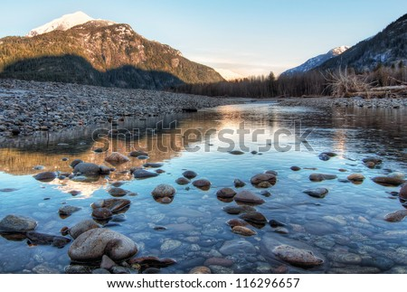 Clear river with rocks leads towards mountains lit by sunset #116296657