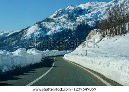 Clear road in the mountains bordered by tall snow. Winter landscape.