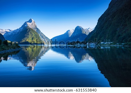 Clear sky in Milford sound, Fjordland national park, south island, New Zealand with a reflection of Mitre peak in the water.