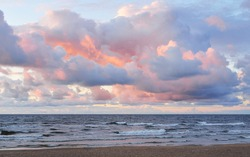 Clear sky with lots of glowing colorful pink cumulus clouds above the Baltic sea shore after thunderstorm at sunset. Dramatic cloudscape. Warm golden sunlight. Picturesque scenery. Fickle weather