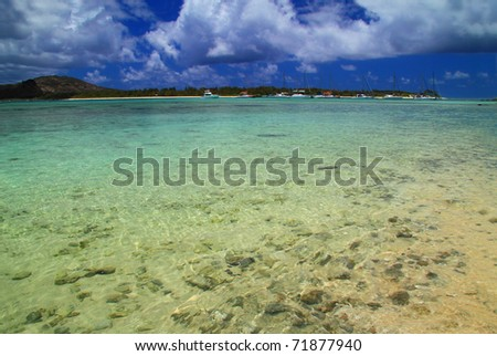 Clear turquoise water with blue sky and boats in the background