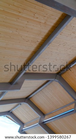 Clear Vertical Vertical Looking up at the roof of a pavilion with brown wooden planks and gray frames
