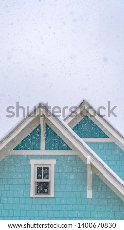 Clear Vertical Vertical Snow falling on a blue home in Daybreak Utah with cloudy sky in the background