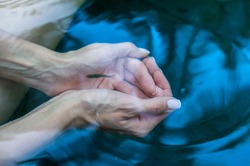 Clear water in the female palms, Female hands cupped together submerged in clean clear blue water