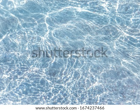 Clear water in the sea, sun glare, waves and sea pebbles. Light blue sea water background