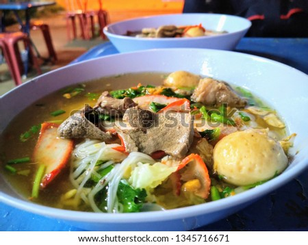 Clear water noodles with chicken and chicken pieces, fresh red meat, and large balls of large amount, large blue plastic bowls focus of front. #1345716671