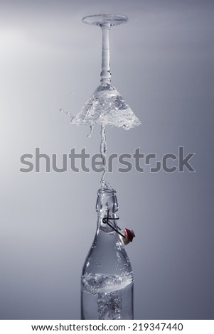 Clear water pour out of bottle splash into a glass with grey back lighting upside down