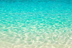 Clear water reflections on shallow sandy beach bottom, Thailand in a summer day