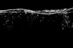 Clear water surface on a black with ripple and bubbles