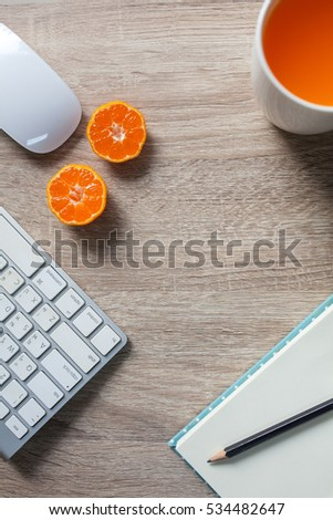 clear wooden office table with notebook, keybord, mouse and orange juice cup. View from above with copy space #534482647