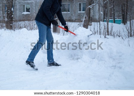 Clearing snow with a shovel in the winter on the street