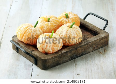 Clementine Oranges Decorated Like Pumpkins on Rustic Wooden Tray #214805191