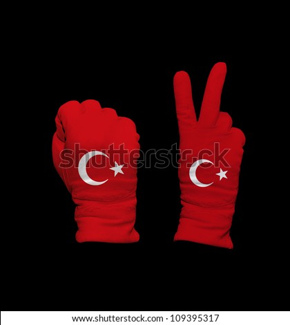 Clenched fist in leather glove, and hand with victory gesture in a glove decorated with Turkey flag