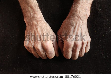 clenched fists of old man on black fabric