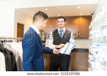 Clerk in formals matching tie with shirt for customer in showroom #1332129386
